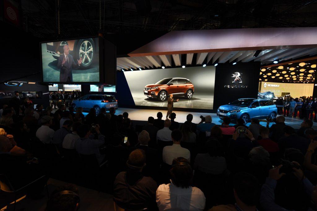 """Um 3008 totalmente renovado (que deve chegar no fim de 2017 ao Brasil), com um design mais moderno e musculoso e painel totalmente digital, incorporando a nova geração do sistema """"i-Cockpit""""; e as mesmas opções de motor (incluindo o THP). A Peugeot também exibe o novo 5008, que virou um SUV de sete lugares"""