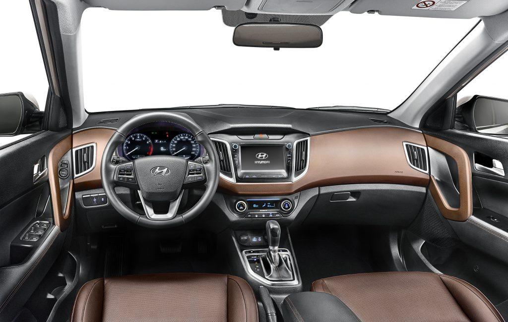 A versão Prestige tem bancos em couro marrom, acabamento das portas e apoio de braços lateral e central em couro preto